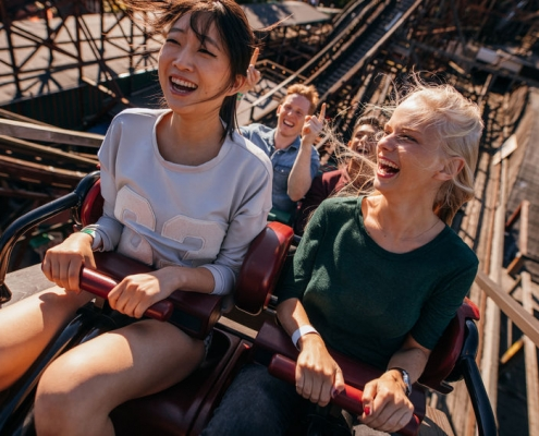 shot of smiling young people riding a roller coaster. young women and men having fun on amusement park ride.